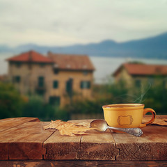 cup of coffee on old wooden table in front of romantic Provence rural landscape. retro filtered image