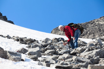 Hiker stepping on sharp stones while climbing the snowy mountain pass
