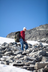 Mature Caucasian hiker in red jacket standing on the top of mountain at steep stony slope