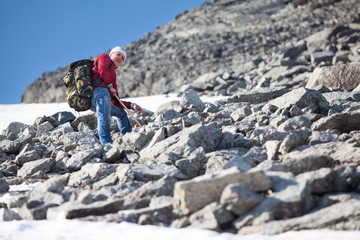 Mature Caucasian hiker climbing with backpack in steep slope mountains at summer season
