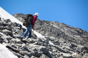 Mature Caucasian hiker looking at the mountain top while resting on the steep slope