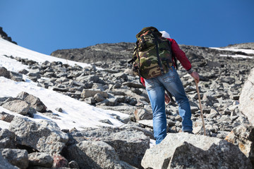 Rear view of hiker climbing on steep stony slope in mountains
