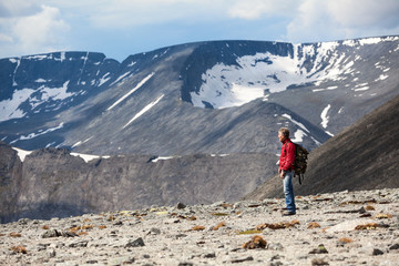 Mature Caucasian hiker looking down at the mountain slope, copy space