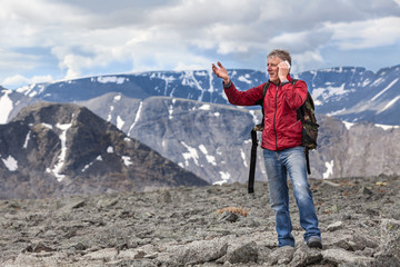 Middle-aged man tells about seen landscape in the mountains, talking on mobile phone