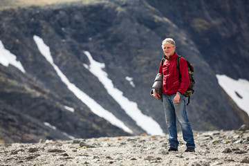 Mature Caucasian hiker with a backpack standing on the mountain plateau, copy space