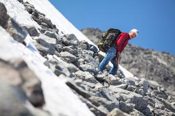 Mature man climbing in mountain at summer season, resting on steep slope