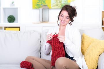 Fototapeta attraktive frau sitzt auf cuch und strickt obraz