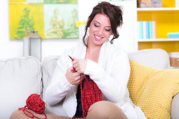 frau braunhaarig sitzt auf couch und strickt einen pulli