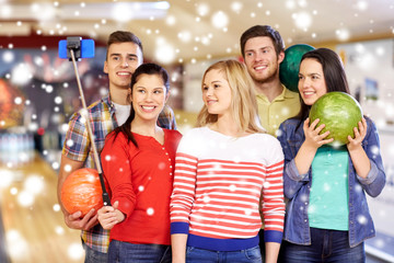 happy friends taking selfie in bowling club