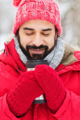 happy man with thermos cup in winter forest