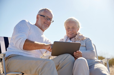 happy senior couple with tablet pc on summer beach