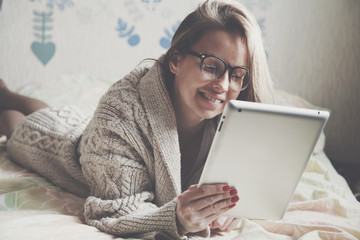 woman lying in bed with digital tablet touching with finger in m