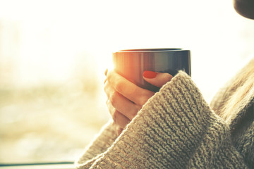 Foto op Canvas Thee hands holding hot cup of coffee or tea in morning sunlight