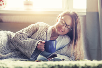 pretty girl reading book with morning coffee lying in bed