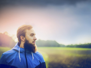 young man with a beard wearing a blue jacket and in profile against green field and sky