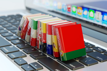 Foreign languages learn and translate education concept, books with covers in colors of national flags of world countries on computer laptop keyboard