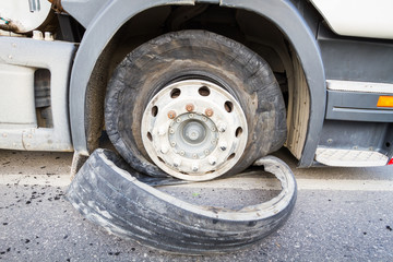 Damaged 18 wheeler semi truck burst tires by highway street