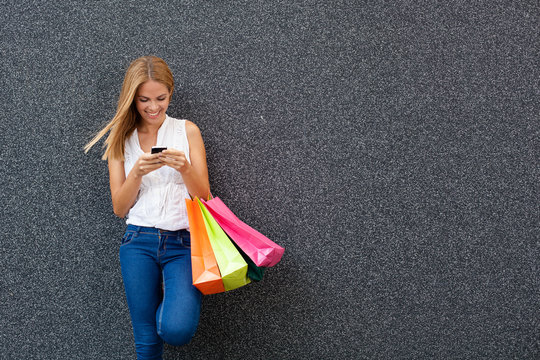 Happy young woman typing a message the phone after shopping