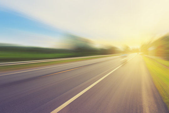 Empty asphalt road in motion blur and sunlight with vintage tone
