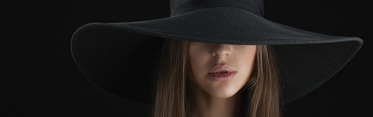 Woman with beautiful lips in broad-brimmed hat.