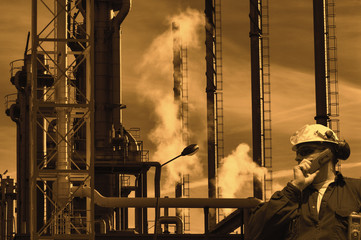 sunset over large oil refinery, worker talking in phone