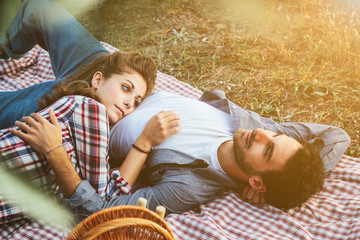 On a late summer day, a pair of young lovers is lying on the grass. The head of the young woman's belly on him. Picture taken from the leaves of olive trees in a field the Tuscany, Italy
