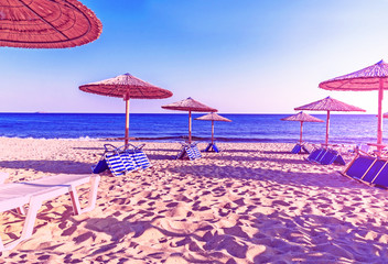 Purple picture of sunbed, straw umbrella on beautiful beach back