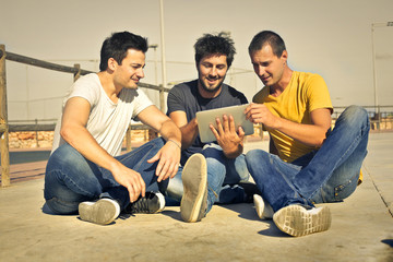 Three friends watching something on a tablet