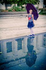 Fillette au parapluie sur la place Lazare Goujon à Villeurbanne