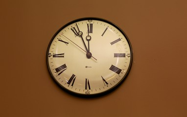 Clock with Roman Numeral characters on a beige wall