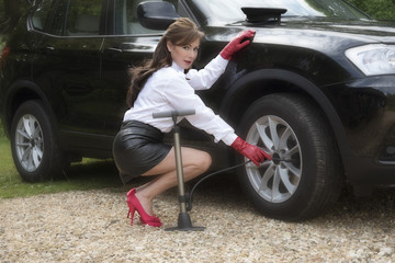 Woman chauffeur in a mini skirt checking tyre pressure and inflating tire