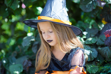Wall Mural - Portrait of happy little girl wearing witch costume with broom