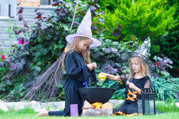 Wall Mural - Adorable little girls in witch costume on Halloween have fun