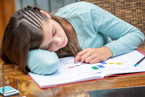 sweet little schoolgirl sad and tired looking depressed suffering     Tired girl doing homework