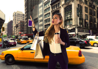 Blond shopping tourist girl calling a yellow Taxi NYC