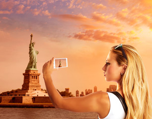 Blond tourist taking photo to Statue of Liberty NYC