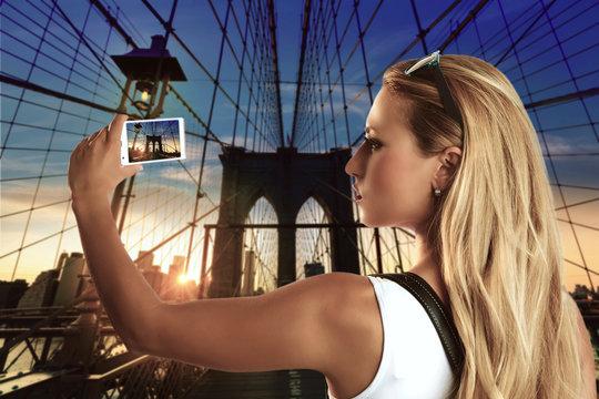 Blond tourist girl taking photo in Brooklyn Bridge