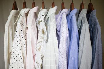A row of assorted business shirts for women on hangers in a clos