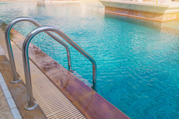 blue swimming pool at hotel with stair