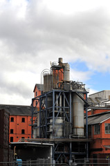 Red factory buildings and metal industrial devices of a sugar refinery with a cloudy sky background.
