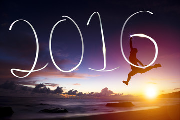 happy new year 2016.young man jumping  and drawing 2016 on beach