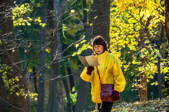 Elderly woman in yellow jacket reading old map in forest