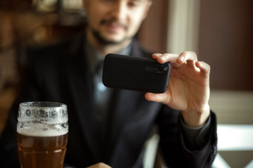 Man with smartphone taking selfie at cafe