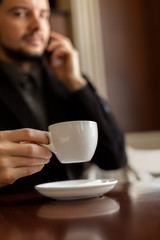 Man in a cafe with a cup of coffee.
