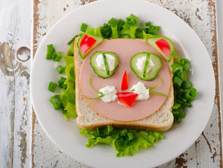 Breakfast with a smiling toast and vegetables.