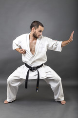 Full length portrait of young man in white kimono and black belt