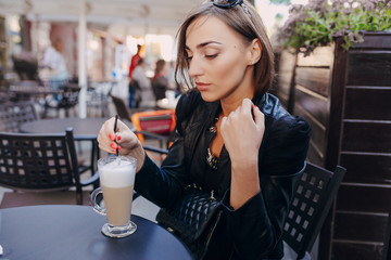 beautiful girl drinking a cappuccino in a cafe