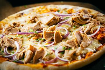 Savory tuna pizza with herbs and onions