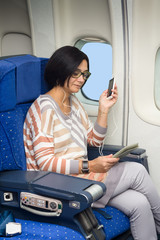 woman passenger in airplane using mobile and  tablet smart devices with headphones