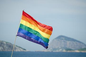 Gay pride rainbow flag flying above the Farme de Amoedo section of Ipanema Beach, in Rio de Janeiro, Brazil